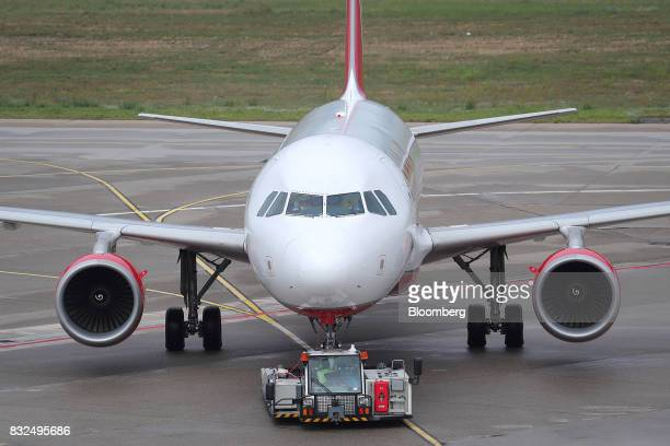 A tow tractor maneuvers a passenger aircraft operated by Air Berlin Plc on the tarmac at Tegel airport in Berlin Germany on Wednesday Aug 16 2017 Air...