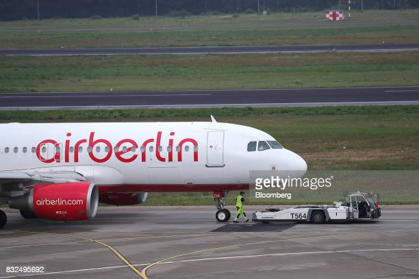 A tow tractor stands beneath the cockpit of a passenger aircraft operated by Air Berlin Plc on the tarmac at Tegel airport in Berlin Germany on...