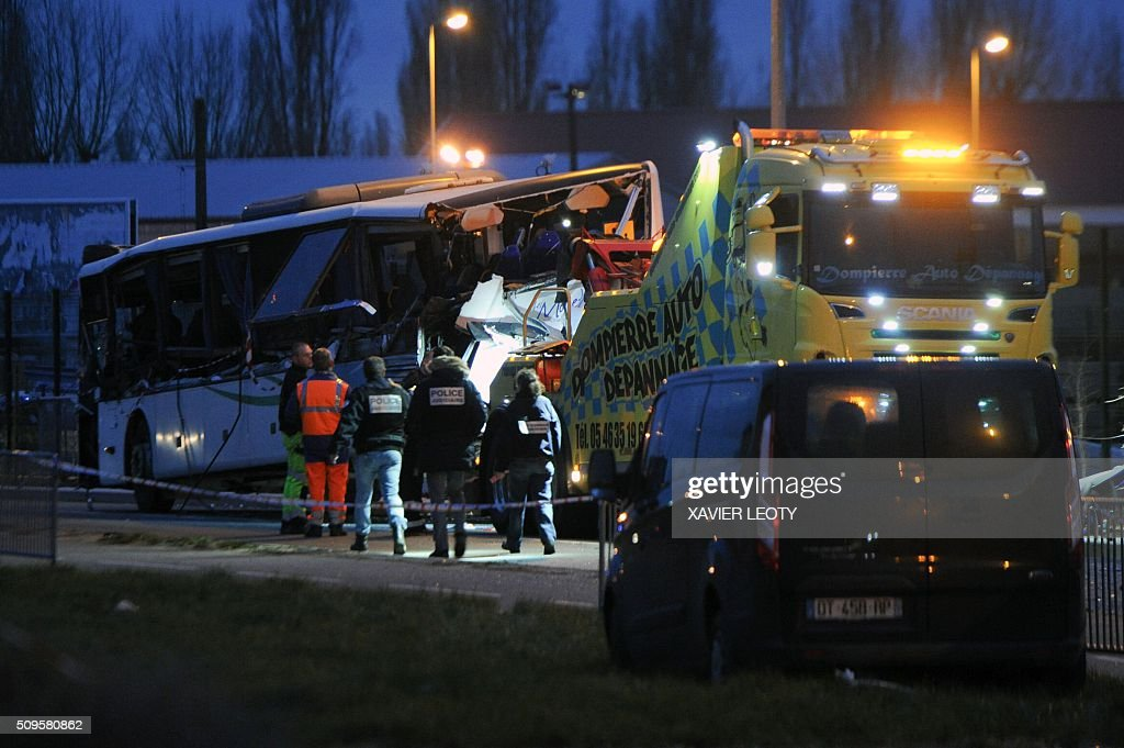 A tow truck carries away the wreckage of a school bus after it crashed into a truck in Rochefort on February 11, 2016, killing at least six children, police said, a day after another road accident involving a school bus left two youngsters dead. The head-on smash with a lorry carrying rubble came around 7:15 am (0615 GMT) in Rochefort in the western Charente-Maritime region. The school bus was carrying about 17 people, and three children suffered minor injuries in the accident, a police source said. / AFP / XAVIER LEOTY