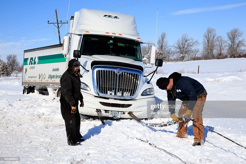 Tow truck driver Tyson House helps trucker Gary Wheeler of Kansas City after his truck slid off the road during large midwest winter storm which brought snow throughout the region on February 22, 2013 in Greensburg, Kansas. The storm dumped at least a foot of snow in Kansas and looks to be headed to the northeast U.S.
