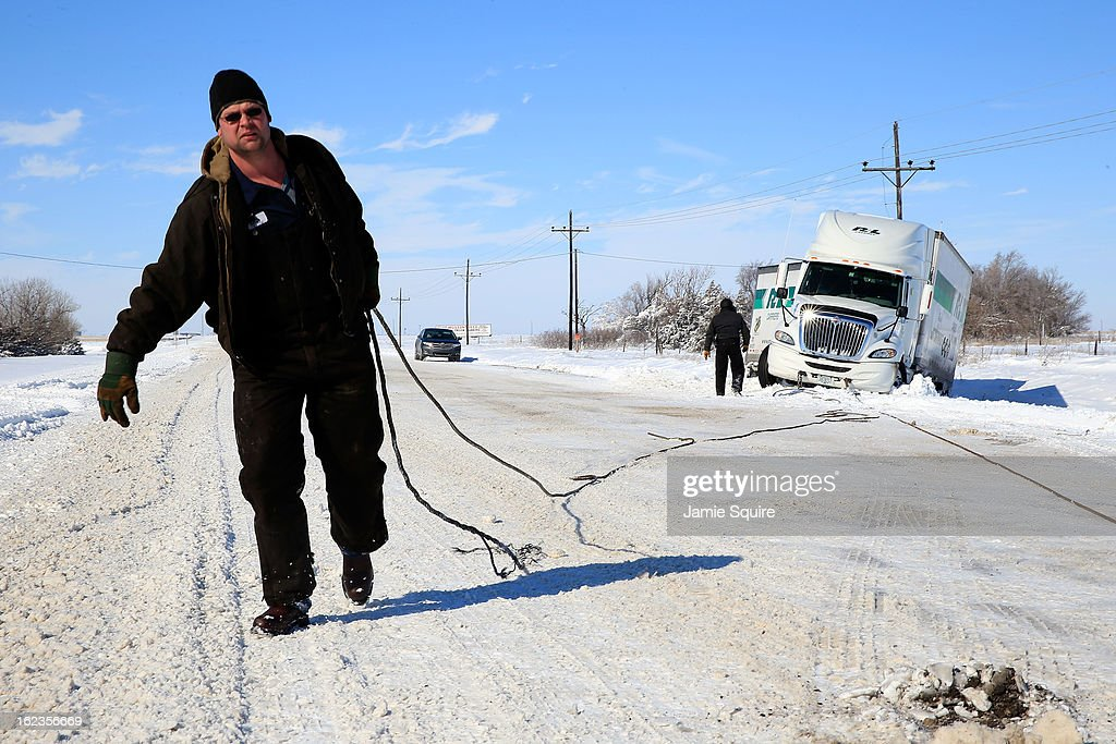Tow truck driver Tyson House helps trucker Gary Wheeler of Kansas City after his truck slid off the road during large midwest winter storm which brought snow throughout the region on February 22, 2013 in Greensburg, Kansas. The storm dumped at least a foot of snow in Kansas and forcasters say it is headed to the northeast U.S.