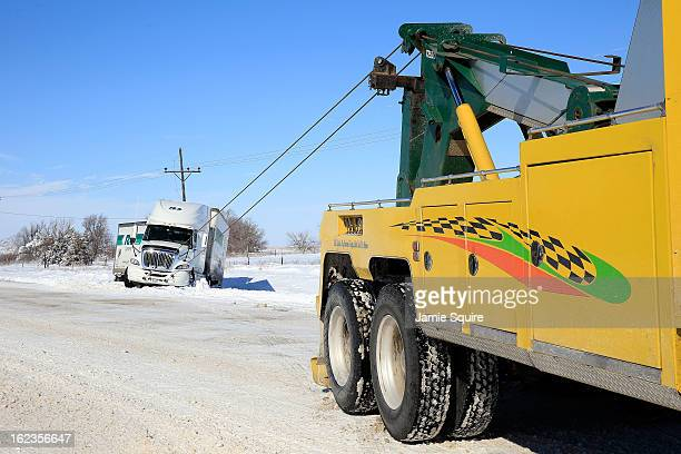 Tow truck drivers extract a semitruck after it slid off the road during large midwest winter storm which brought snow throughout the region on...
