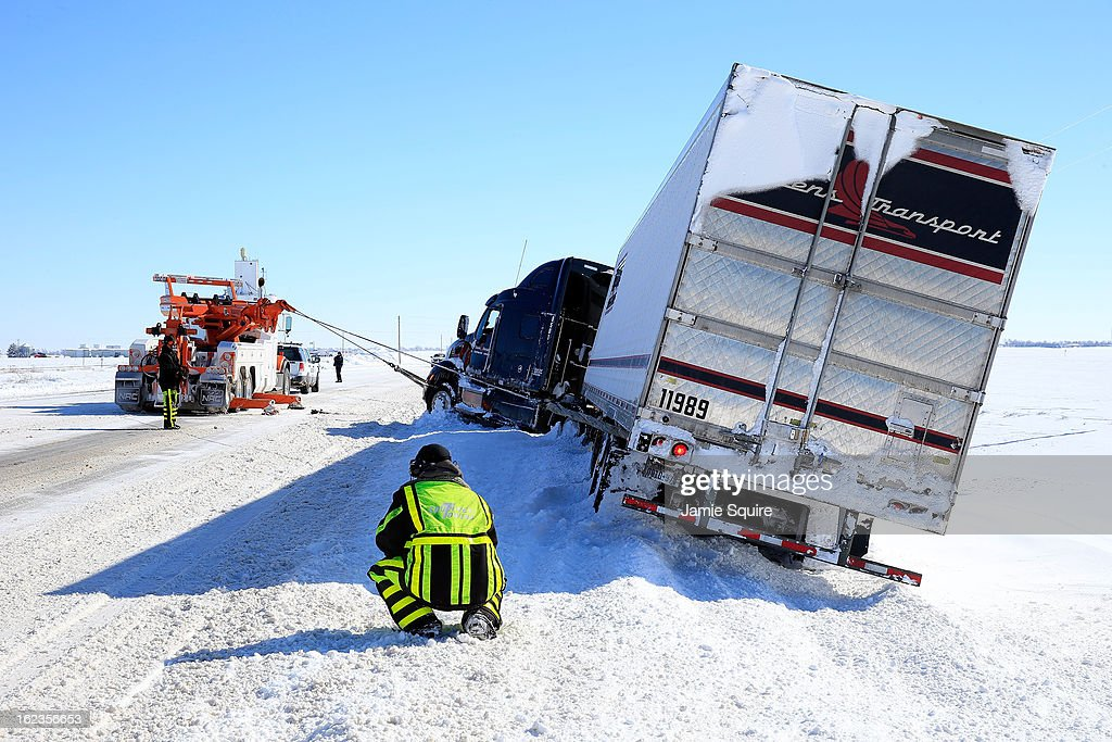 Tow truck drivers extract a semi-truck after it slid off the road during large midwest winter storm which brought snow throughout the region on February 22, 2013 in Greensburg, Kansas. The storm dumped at least a foot of snow in Kansas and forcasters say it is headed to the northeast U.S.