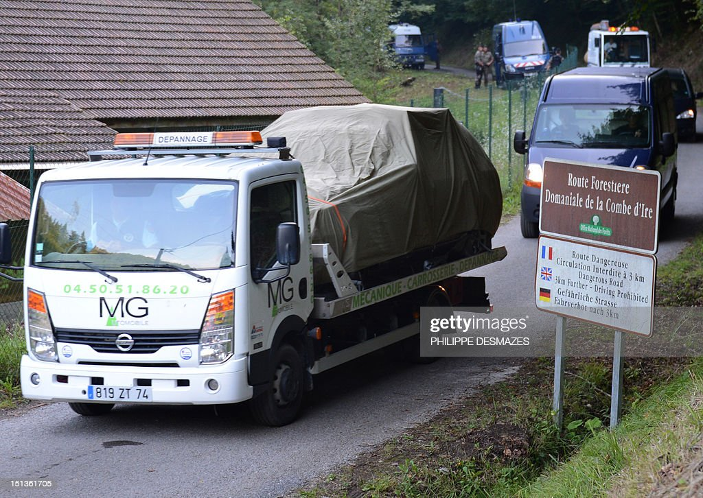 A tow truck escorted by French gendarmes on the 'Combe d'Ire' road carries the car in which three people were shot dead on September 6, 2012 in the French Alpine village of Chevaline. A four-year-old girl spent hours curled up under her mother's body and miraculously survived the deadly attack that left her father, mother and grandmother dead and her elder sister seriously injured, officials said. AFP PHOTO/PHILIPPE DESMAZES