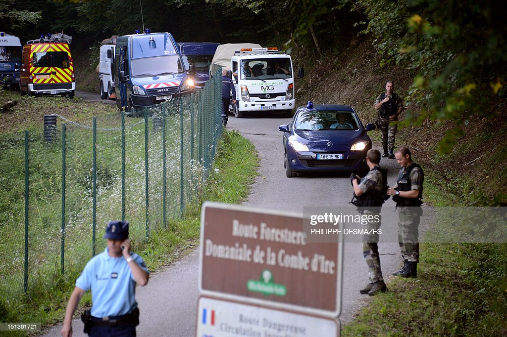 A tow truck escorted by French gendarmes on the 'Combe d'Ire' road carries the car in which three people were shot dead on September 6, 2012 in the French Alpine village of Chevaline. A four-year-old girl spent hours curled up under her mother's body and miraculously survived the deadly attack that left her father, mother and grandmother dead and her elder sister seriously injured, officials said.