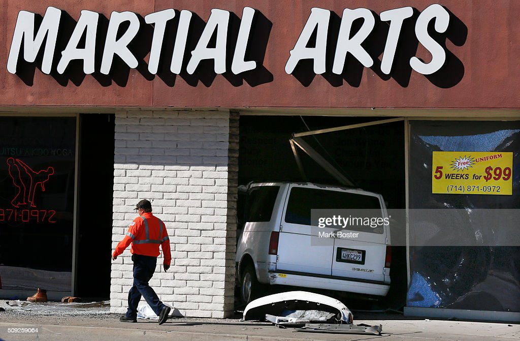 A tow truck operator walks past a van that crashed through the front window of the Moo Yea Do martial arts studio in the 600 block of South Euclid in Fullerton, injuring the driver February 9, 2016