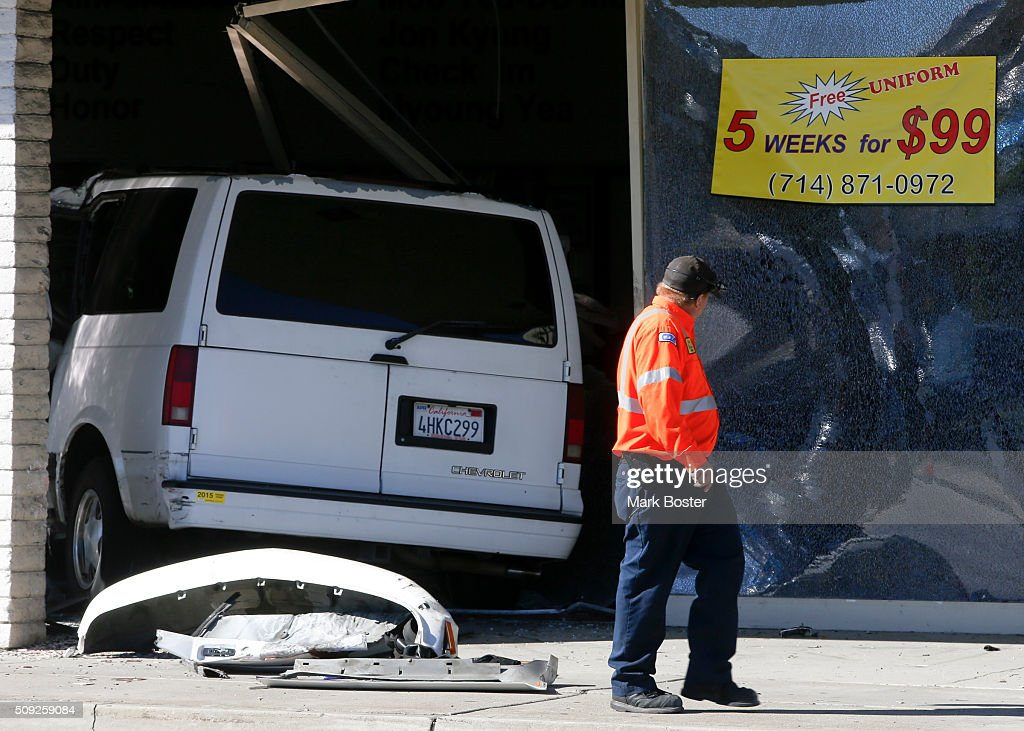 A tow truck operator walks past an accident in the 600 block of South Euclid Avenue in Fullerton at the Moo Yea Do martial arts studio where a van crashed through the front window injuring the driver February 9, 2016