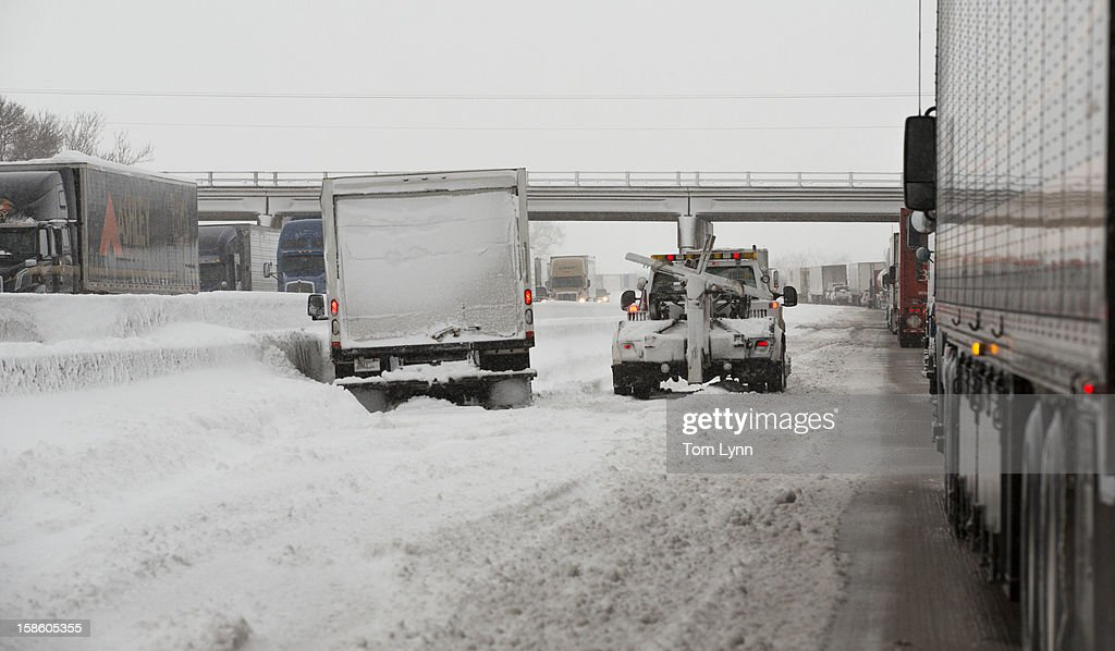 A tow truck prepares to aid a stranded truck on Interstate I-90 December 20, 2012 near Madison, Wisconsin. The State Patrol was warning motorists to stay home as a paralyzing winter storm bore down on Wisconsin In the first significant snowstorm to hit southern Wisconsin in two winters.