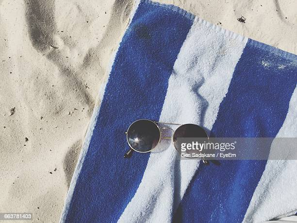 Towel And Sunglasses On Sand At Beach