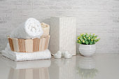 Towel in wooden bucket with ceramic vase, ceramic bird and houseplant on white marble teble with brick wall background.