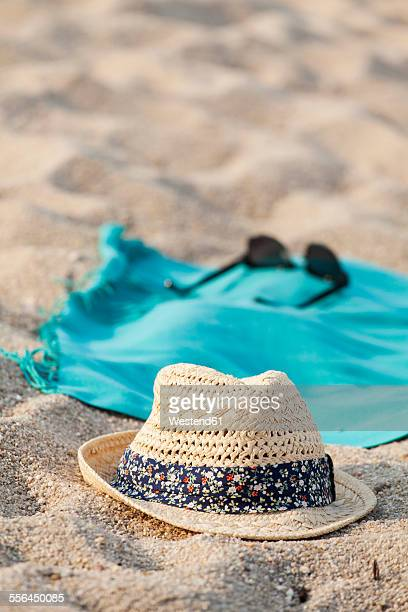 Towel, sunglasses and straw hat on sandy beach