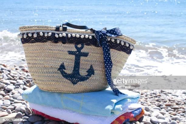 Towels and Beach Bag On Beach Against Blue Sea