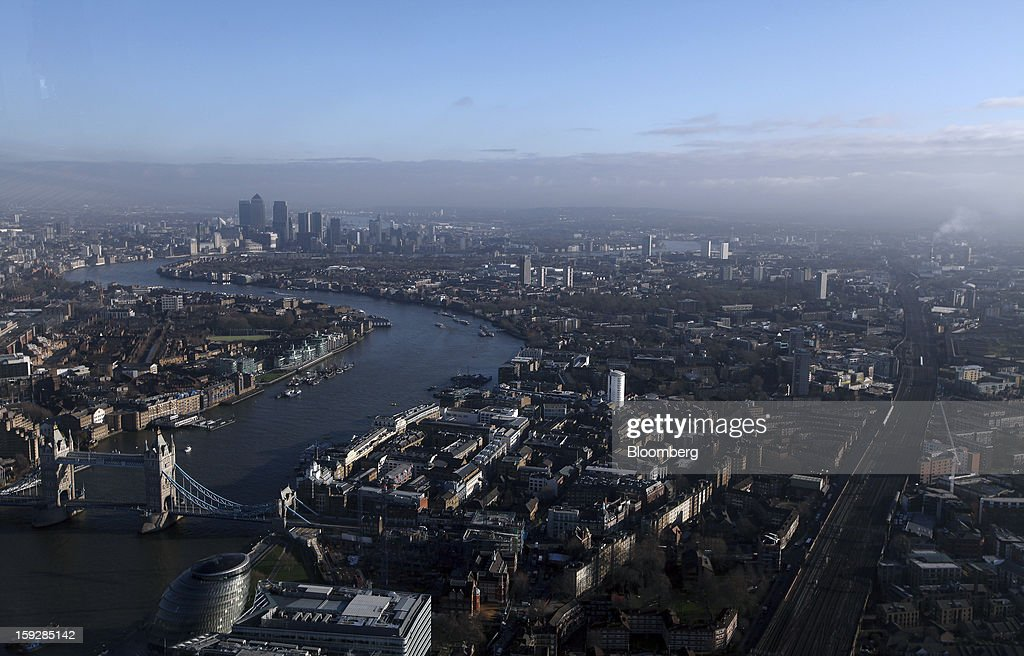 Tower Bridge, bottom left, is seen spanning the River Thames, in front of the Canary Wharf business and financial district viewed from 'The View From The Shard', a series of viewing galleries near the top of the Shard tower in London, U.K., on Wednesday, Jan. 9, 2013. The Shard, which stands at 309.6 meters on London's South Bank, is owned by LBQ Ltd., which brings together the State of Qatar (the majority shareholder) and Sellar Property Group Ltd., with non-equity funding by Qatar National Bank. Photographer: Chris Ratcliffe/Bloomberg via Getty Images