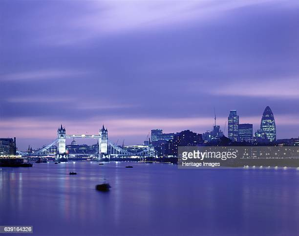 Tower Bridge London c19902010 Tower Bridge and the London skyline at nightfall with the river Thames in the foreground A combined bascule and...
