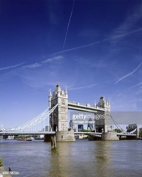 Tower Bridge London c19902010 Tower Bridge and the river Thames Vapour trails in the sky with Gherkin Swiss Re Tower framed by bridge A combined...