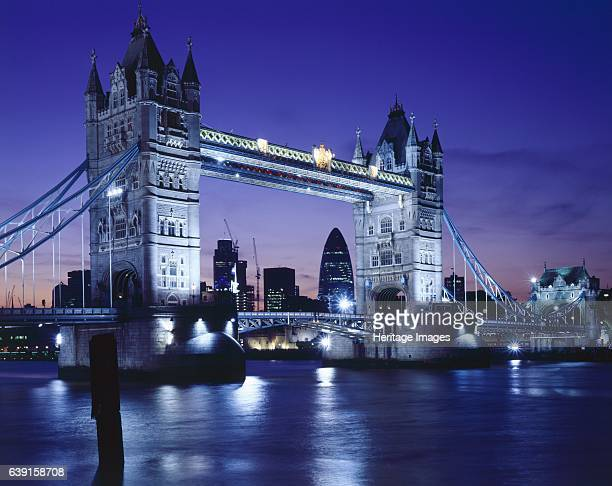 Tower Bridge London c19902010 Tower Bridge at night with the river Thames in the forground and the Gherkin Swiss Re Tower framed by the bridge A...