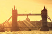Sunbeams over Tower Bridge and St. Paul's Cathedral Dome before sunset.