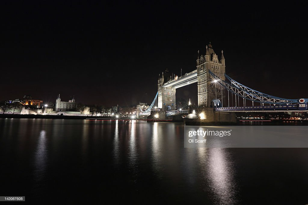 Tower Bridge (R) spanning the river Thames and the Tower of London (L) are illuminated at night on March 28, 2012 in London, England.