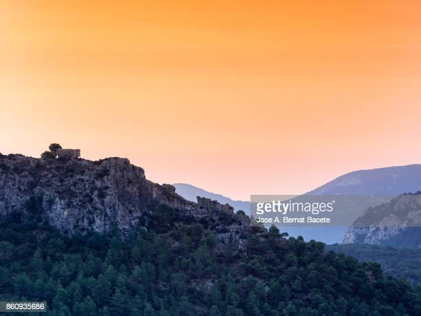 Tower of an ancient castle on silhouettes of a forest of trees in the hillside of a mountain in a sunset with an orange sky, Valencian Community, Spain