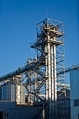 Tower of modern metal grain elevator with silos on blue sky background.