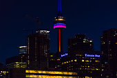 Tower or Canadian National Tower lit on at night displaying variety of colors The Toronto tower is a popular tourist attraction in Canada