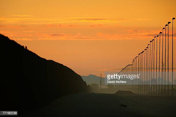 Towering light poles and a wall of metal recently constructed by National Guardsmen form a doublefence border barrier in a dusty nomans land of...