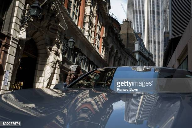 Towers and architecture of Drapers' Hall including the Atlantes figures by sculptor HA Pegram reflected in the bonnet of a car parked in Throgmorton...