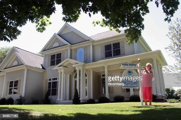 Town and Country Real Estate Owner/broker Gail Lockberg places a for sale sign in front of a new home in Wellesley Massachusetts on Saturday July 23...