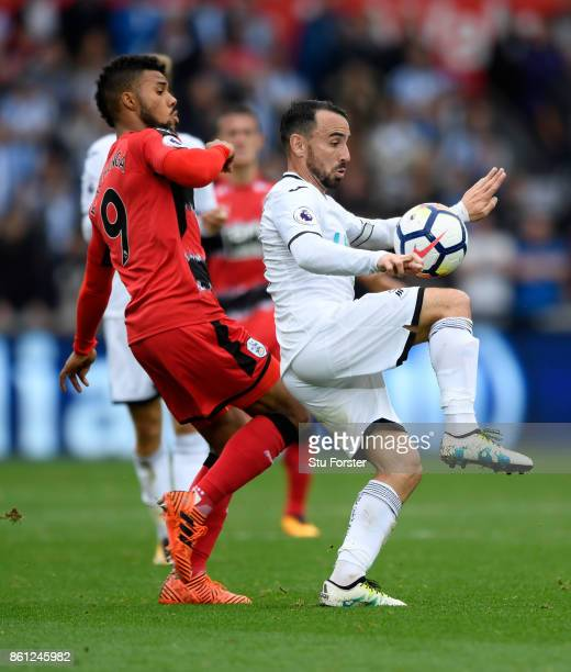 Town player Elias Kachunga challenges Leon Britton of Swansea during the Premier League match between Swansea City and Huddersfield Town at Liberty...