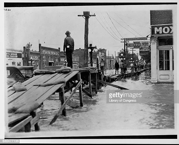 Townspeople walk on a temporary wooden sidewalk above floodwaters in Greenville Mississippi | Location Walnut and Main Streets Greenville Mississippi...