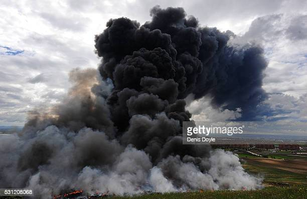 Toxic smoke rises over the housing estate of Nueva Sesena near Madrid after an illegal tyre dump went on fire on May 13 2016 in Sesena Nuevo Spain...