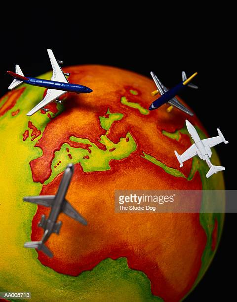 Toy Airplanes Flying Over a Globe