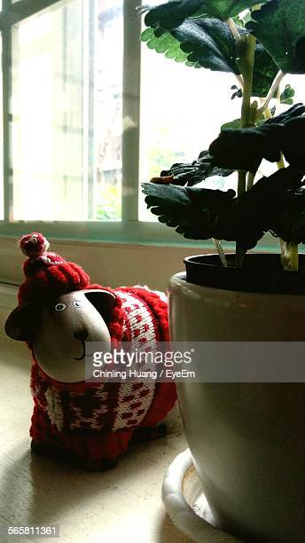 Toy Animal With Woolen Clothing Beside Potted Plant