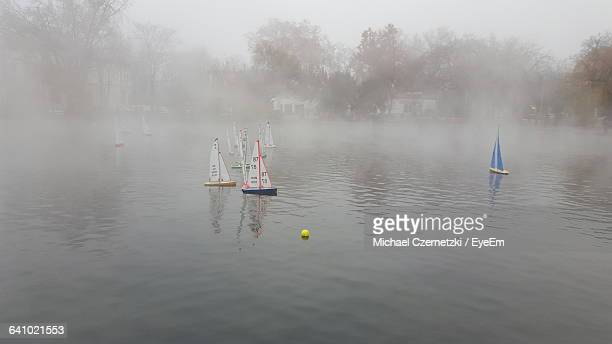 Toy Boats Sailing On Lake At Race During Foggy Weather