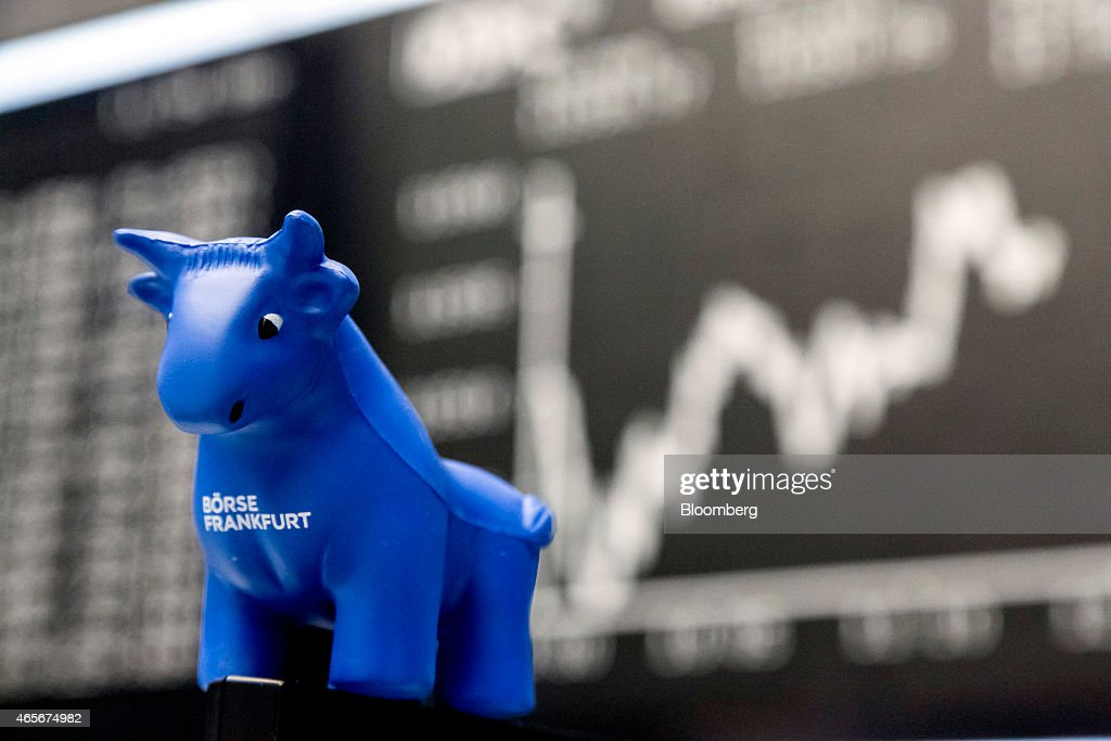 A toy bull figurine sits on a trader's computer screen as the DAX Index curve sits on a board beyond at the Frankfurt Stock Exchange in Frankfurt...