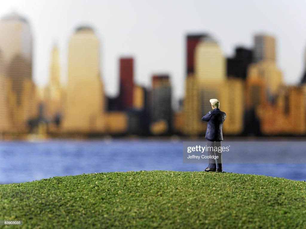 Toy businessman looking at city : Stock Photo