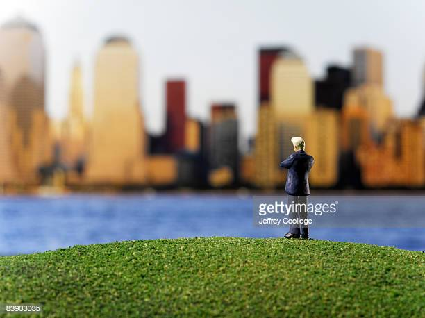 Toy businessman looking at city