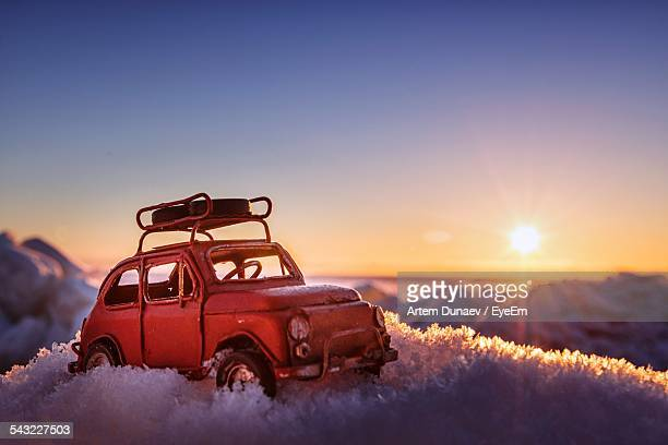 Toy Car On Frozen Field Against Sky During Sunset