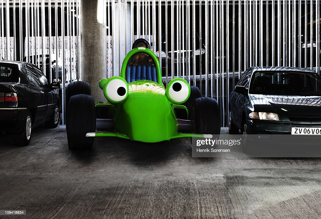 Toy car parked among real cars in parking house
