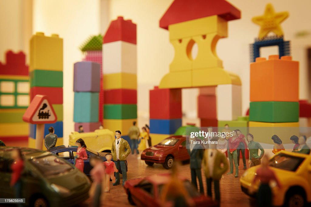Toy cars and figurines in pretend plastic block town : Stock Photo
