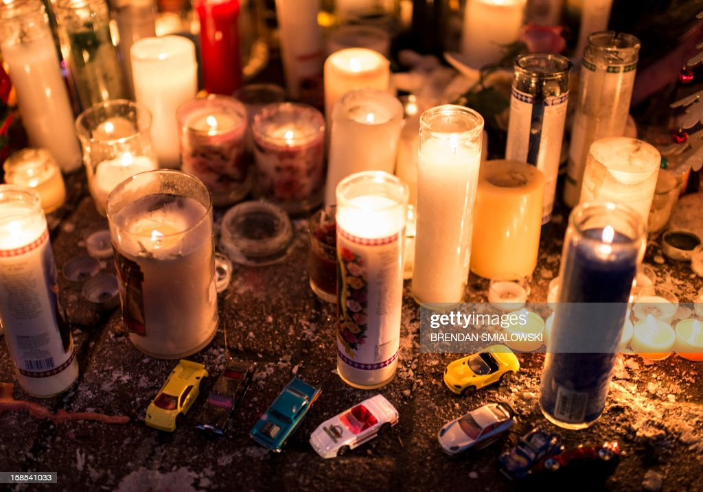 Toy cars are seen with candles at a makeshift memorial on December 18, 2012 in Newtown, Connecticut. Students in Newtown, excluding Sandy Hook Elementary School, returned to school for the first time since last Friday's shooting at Sandy Hook which took the live of 20 students and 6 adults. AFP PHOTO/Brendan SMIALOWSKI
