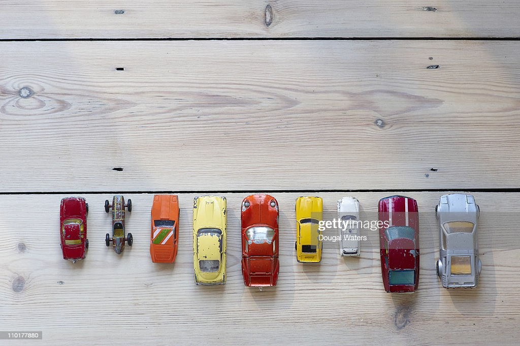 Toy cars lined up in a row on floor : Stock Photo