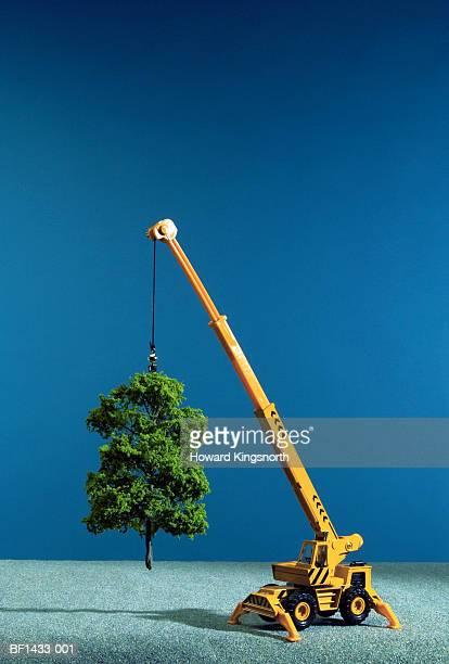Toy crane 'lifting' artificial tree, close-up