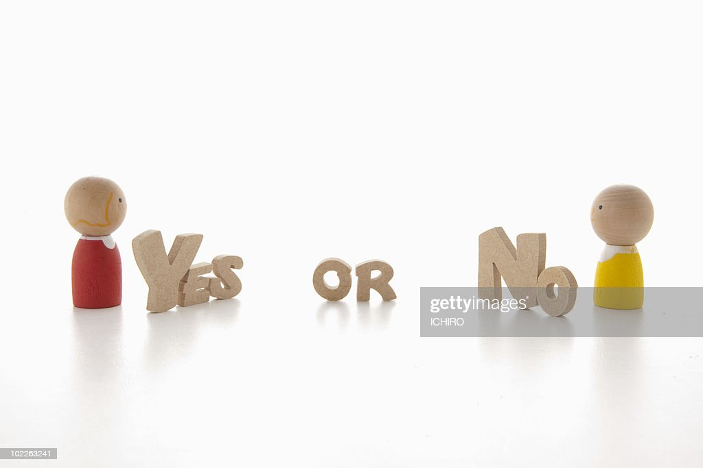 Toy doll and 'Yes or No' sign : Stock Photo