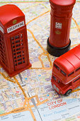 Toy double-decker bus, phone booth, and Royal Mail pillar mailbox on map of London
