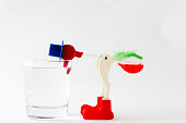 """Toy """"drinking bird"""" on a white background. Drinking bird leaned into a glass of water."""