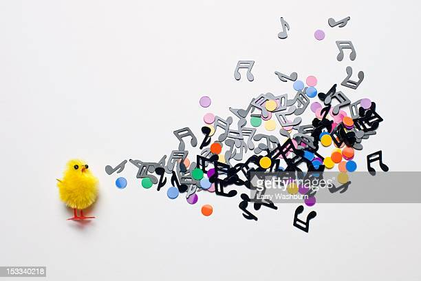 A toy Easter chick next to a group of musical notes and confetti