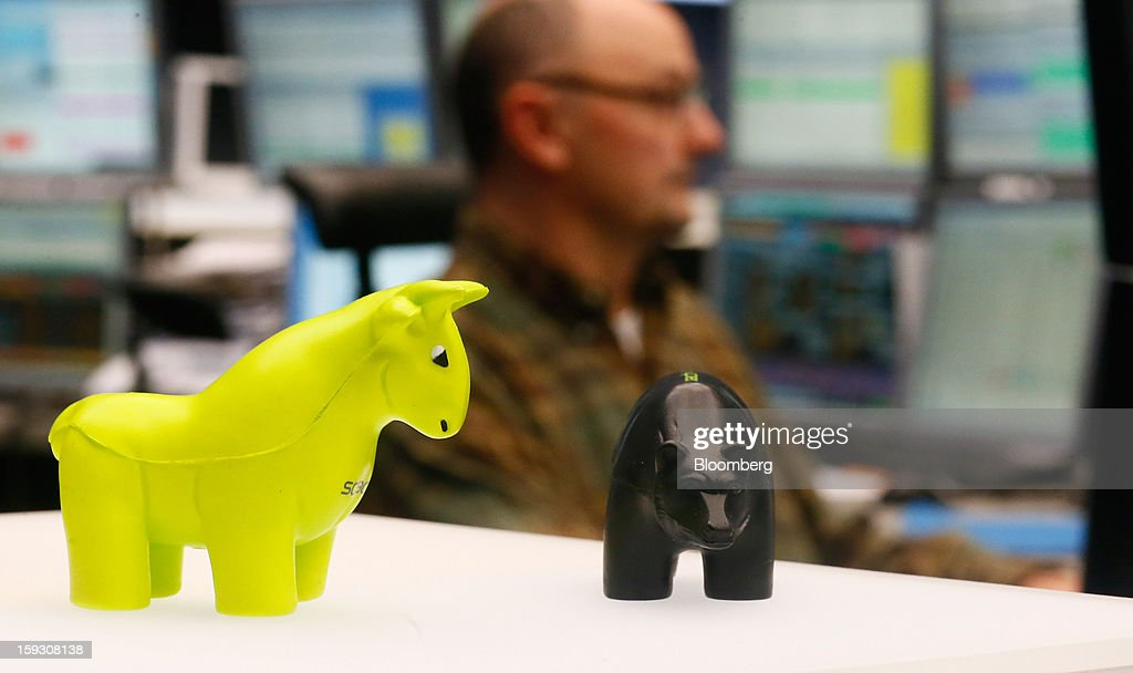 Toy figures of a bull, left, and a bear stand on a counter while a trader works at his computer screens at the Frankfurt Stock Exchange in Frankfurt, Germany, on Friday, Jan. 11. 2013. European stocks pared their decline as Italy's borrowing costs dropped at a debt sale, offsetting concern that China has less room for monetary easing after a reported showed inflation increased more than estimated. Photographer: Ralph Orlowski/Bloomberg via Getty Images