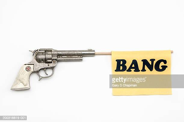 Toy gun with flag coming out of barrel reading 'bang'