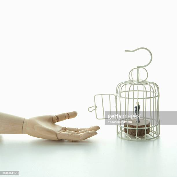 Toy hand, miniature businessman figure in the cage